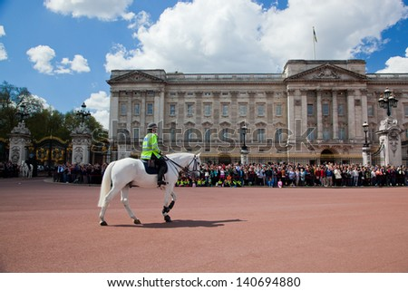LONDON - MAY 17: British Royal guards riding on horse and perform the Changing of the Guard in Buckingham Palace on May 17, 2013 in London, UK - stock photo