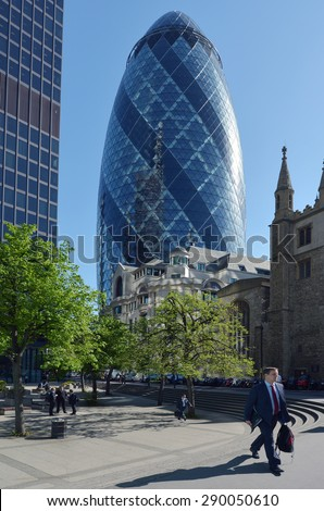LONDON - MAY 13 2015: Businessmen under 30 St Mary Axe tower.The building has become an iconic symbol of London and is one of the city's most widely recognized examples of contemporary architecture. - stock photo