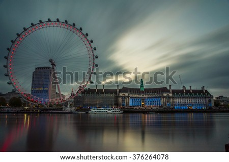 London-May 4: London City landmarks including London eye and London county hall with the river Thames reflection and grey rain clouds in early morning on May 4, 2015 - stock photo