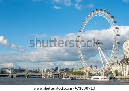 LONDON - MAY 24: London Eye, the giant ferris wheel at the South bank of River Thames in London, England, under cloudy blue sky on May 24, 2016.