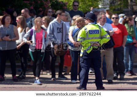 LONDON - MAY 13 2015:Metropolitan Police Service officer on guard duty.Since Jan 2015 Police across Britain have been put on high alert and warned that they may be targeted in terror attacks - stock photo