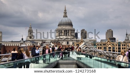 LONDON-MAY 28 :People walking across a footbridge Millennium Bridge. Background is St Paul's cathedral in London. Bridge was opened 10 June 2000. View on May 28, 2012