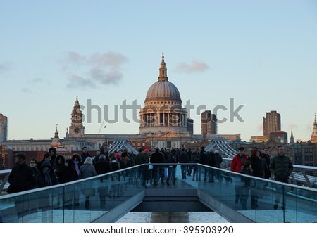 LONDON - MAY 5:People walking over Millennium bridge at dusk. St Pauls cathedral in the background on May 5, 2015 in London .  - stock photo
