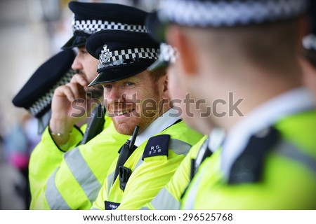 LONDON - MAY 30: Police stand guard during a rally against government public sector spending cuts following the re-election of the conservative party on May 30, 2015 in London, UK. - stock photo