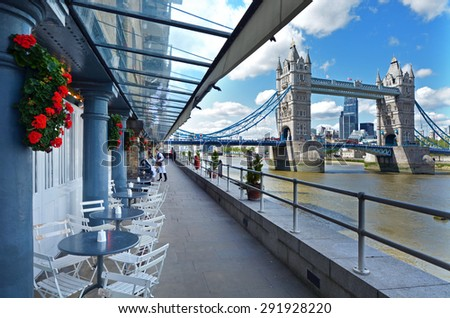 LONDON - MAY 13 2015:Restaurant over looking Tower Bridge in Shad Thames or Butler's Wharf in London England UK.It is an historic riverside street next to Tower Bridge in Bermondsey, London, England. - stock photo