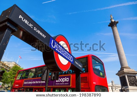 LONDON - MAY 19: sign of the London Underground and a red double decker bus at the Trafalger Square on May 19, 2014 in London. The London Underground is the oldest underground of the world.