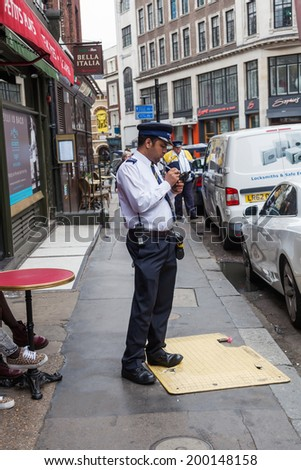 LONDON - MAY 21: street scene in London with unidentified people and a civil encounter officer who writes a ticket on May 21, 2014 in London. London is the most populous city in Europe.