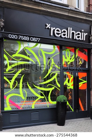 LONDON - MAY 2, 2015. Window graphics on a hairdressing salon at Cale Street, in the Royal borough of Kensington & Chelsea, London, UK. - stock photo