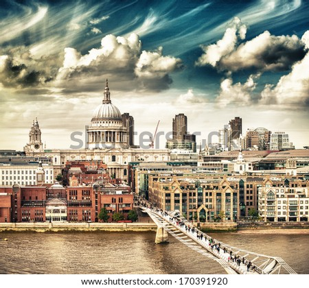 London. Metal structure of Millennium Bridge with Saint Paul Cathedral in background.