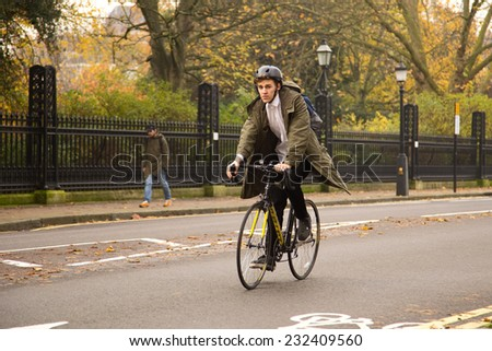LONDON - NOVEMBER 20TH: Unidentified man rides a bicycle on November the 20th, 2014 in London, England, UK. The london authorities are working to make london more cycle friendly. - stock photo