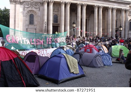 LONDON- OCT 23: Anti-capitalist demonstrators protest and camp in the famous St. Pauls churchyard on Oct. 23, 2011 in London, England. The protests are being held in capital cities all over the world. - stock photo