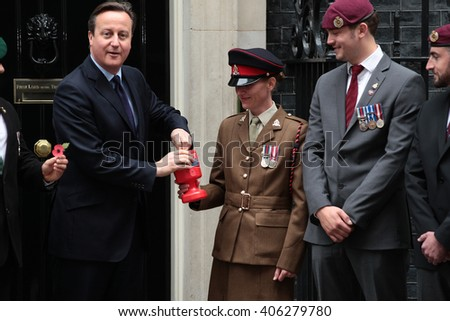 LONDON - OCT 22, 2015: Prime Minister David Cameron buys his remembrance poppy from Corporal Linda for this years Poppy appeal at 10 Downing Street on Oct 22, 2015 London