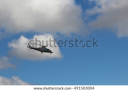 London, October 2016 A silver helicopter is seen against the background of a blue sky with white clouds