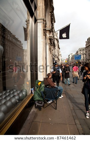LONDON - OCTOBER 9: Consumers keen to purchase the iPhone 4S camp outside the Regent Street Apple Store on October 9, 2011 in London. The iPhone 4S is released in the UK on October 14, 2011.