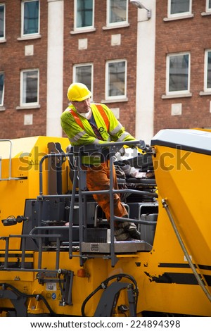 LONDON - OCTOBER 18TH: Unidentified workman using a cold milling machine on October 18th, 2014 in London, England, UK. Power Plane are the most modern Wirtgen planing fleet in the UK - stock photo