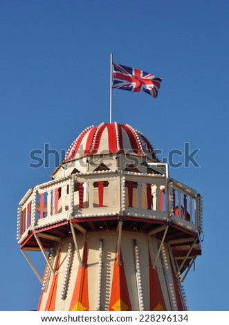 LONDON - OCTOBER 27. The Union flag flies over a Helter Skelter on October 27, 2014, at Stratford in the Borough of Newham, a district undergoing regeneration in east London, UK. - stock photo