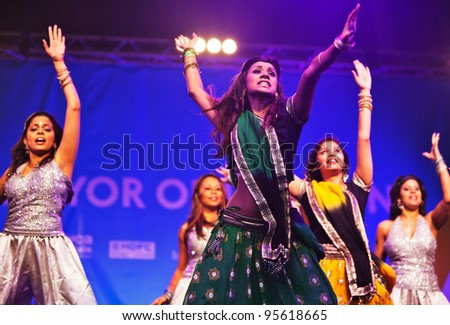 LONDON - OCTOBER 16: Unidentified dancers perform traditional and modern adaptations of Indian dance at the Diwali Festival of Light in Trafalgar Square on October 16, 2011 in London. - stock photo
