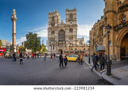 LONDON - OCTOBER 5, 2014: Westminster Abbey is a large gothic church and the traditional place of coronation for English monarchs and tourists walking in front of the gate. - stock photo