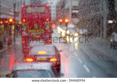 London rain view to red bus through rain-specked window - stock photo
