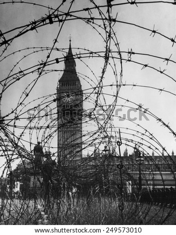 London's Big Ben with barbed wire entanglement and soldiers on guard during World War 2. Ca. 1940-41. - stock photo
