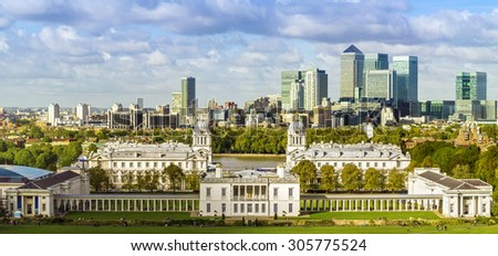 London's National Maritime Museum and skyscrapers of Canary Wharf from Greenwich park - stock photo