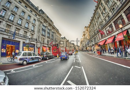 LONDON - SEP 30: Tourists walk in city streets, September 30, 2012 in London. More than 20 million people visit the city every year. - stock photo