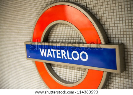 LONDON - SEP 27: Waterloo  underground tube station sign shines on September 27, 2012 in London, England. London's underground railway is the oldest in the world, dating back to 1863 - stock photo