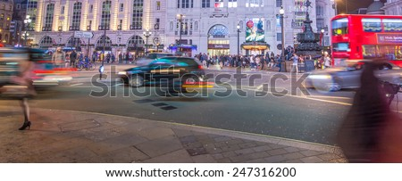 LONDON - SEPTEMBER 27 : Motion blurred traffic and people pass the Trocadero in Piccadilly Circus, London on September 27, 2013.The building was originally a restaurant and is now an entertainment hub - stock photo