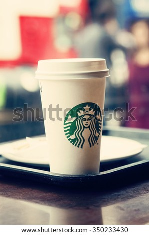 LONDON - September 1, 2015: Starbucks coffee in paper cup with cap.  Starbucks is the world's largest coffeehouse company - stock photo