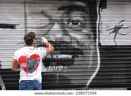 LONDON - SEPTEMBER 27. Street artist at work on shop shutter on September 27, 2014 in Hanbury Street at Shorditch in the Borouh of Tower Hamlets, east London, UK.