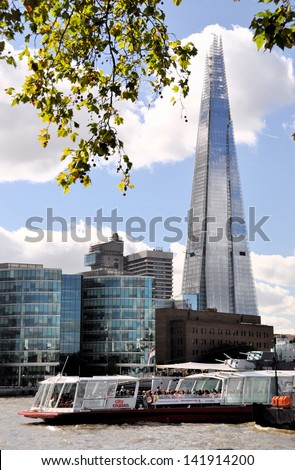 LONDON - SEPTEMBER 29. The Shard skyscraper nearing completion with Thames river boats in the foreground from the north bank on September 29, 2012 in central London, UK. - stock photo