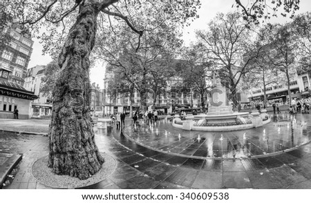 LONDON - SEPTEMBER 28, 2012: Tourists enjoy city streets on a rainy day. The city attracts more than 15 million people every year.