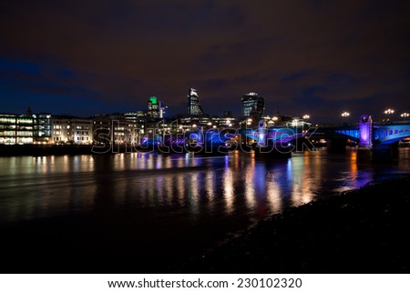 London skyline at night with reflections off the river Thames
