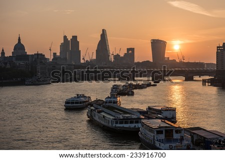 London skyline seen from Waterloo Bridge at sunrise with St Paul's Cathedral, skyscrapers  including The Gherkin, the Cheesegrater, 20 Fenchurch Street and boats moored in the river Thames.