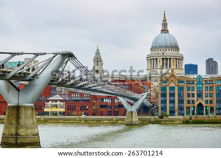 London skyline with St. Paul's cathedral, river Thames and the only pedestrian bridge. Focus on the bridge - stock photo