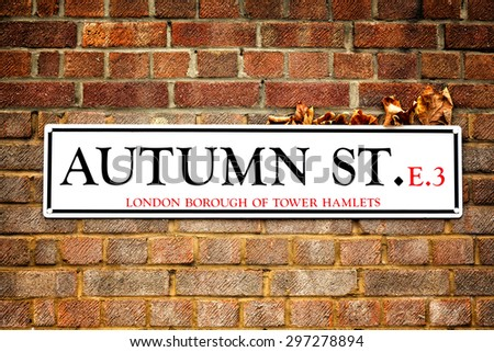 London street sign for Autumn St in Tower Hamlets, East London. The sign has dry autumn leaves caught between it and the red brick wall, highlighting the autumn leaves and Autumn Street concept.  - stock photo