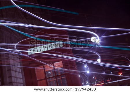 London telephone box and Big Ben in background at night. With light trails. - stock photo