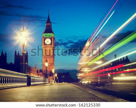 London, the UK. Red bus in motion and Big Ben, the Palace of Westminster at night. The icons of England - stock photo