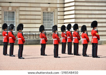LONDON, UK a?? JUNE 12, 2014: British Royal guards perform the Changing of the Guard in Buckingham Palace  - stock photo