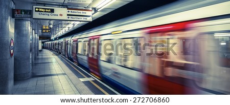 LONDON, UK -APRIL 19,  2015 : A moving train arriving at a London Underground station platform, special photographic processing. - stock photo