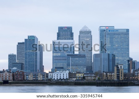 LONDON, UK - APRIL 07, 2015: Canary Wharf skyline over the River Thames at dusk. Canary Wharf is a major business district located in Tower Hamlets.