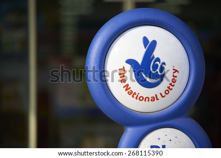 LONDON, UK - APRIL 07: Close up of blue National lottery sign in front of shop, showing its crossed fingers logo. On 07 April 2015. - stock photo