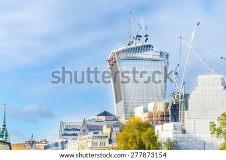 LONDON, UK - APRIL 24, 2014: Famous Walkie Talkie building still keeps iconic glass wall cowered. Wall was covered after it had started reflect very strong sun hit down on properties, roads and cars - stock photo