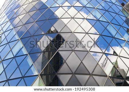 LONDON, UK - APRIL 24, 2014: Ghirkin building glass windows texture reflects the sky. The modern glass buildings of the Swiss Re Gherkin, is 180 meters tall, stands in the City of London - stock photo