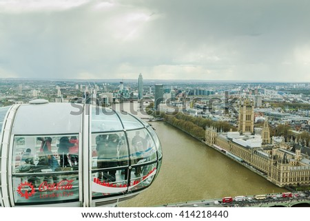 LONDON,UK  - APRIL 26, 2016 Group of tourist enjoy watching aerial view of London from London Eye capsule attraction.