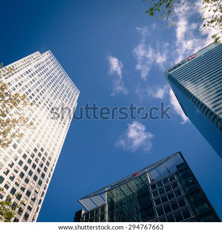 LONDON, UK - 27 APRIL 2015: Low angle view of converging skyscrapers set against a blue spring sky.  The iconic Canary Wharf tower is to the left with HSBC Tower (right) and Bank of America (centre).