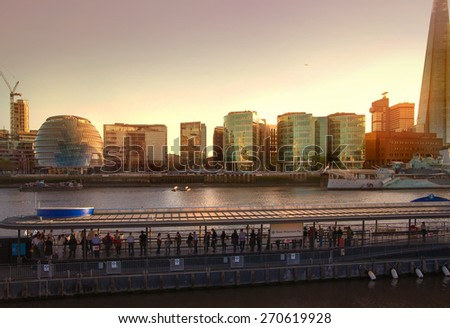 LONDON, UK - APRIL 15, 2015: Modern buildings on the south bank of river Thames walk in sunset. Office centre, theatre and  London city hall building - stock photo