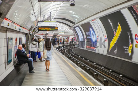 LONDON, UK - APRIL 22, 2015: People waiting at underground tube platform for train arrives - stock photo
