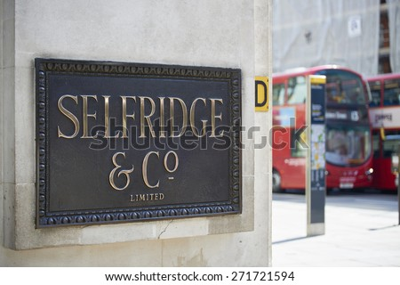 LONDON, UK - APRIL 22: Shop sign at the corner of famous department store Selfridge & Co., in Oxford Street, with red double-decker bus in the background. April 22, 2015 in London. - stock photo