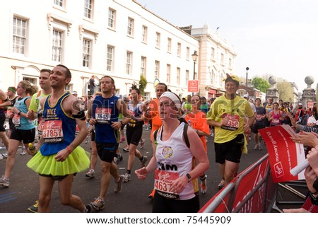 LONDON, UK-APRIL 17: Some of the thousands of runners in the Famous  London Marathon race make their way through the streets in Greenwich on April 17, 2011 in London UK. - stock photo